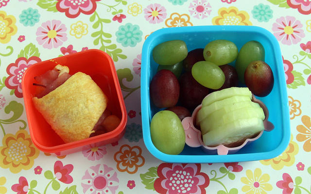 Kindergarten snack with cheesy ham roll, grapes and cukes